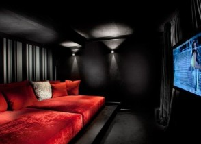 Contemporary-Media-Room-Dark-Feel-With-Red-Bed-Fold-Up-Couch-Bed-And-Curtains-Behind-TV-Also-Add-To-Sensual-Feel